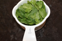 Measure 2/3 cup cilantro and add to blender to food procesor.